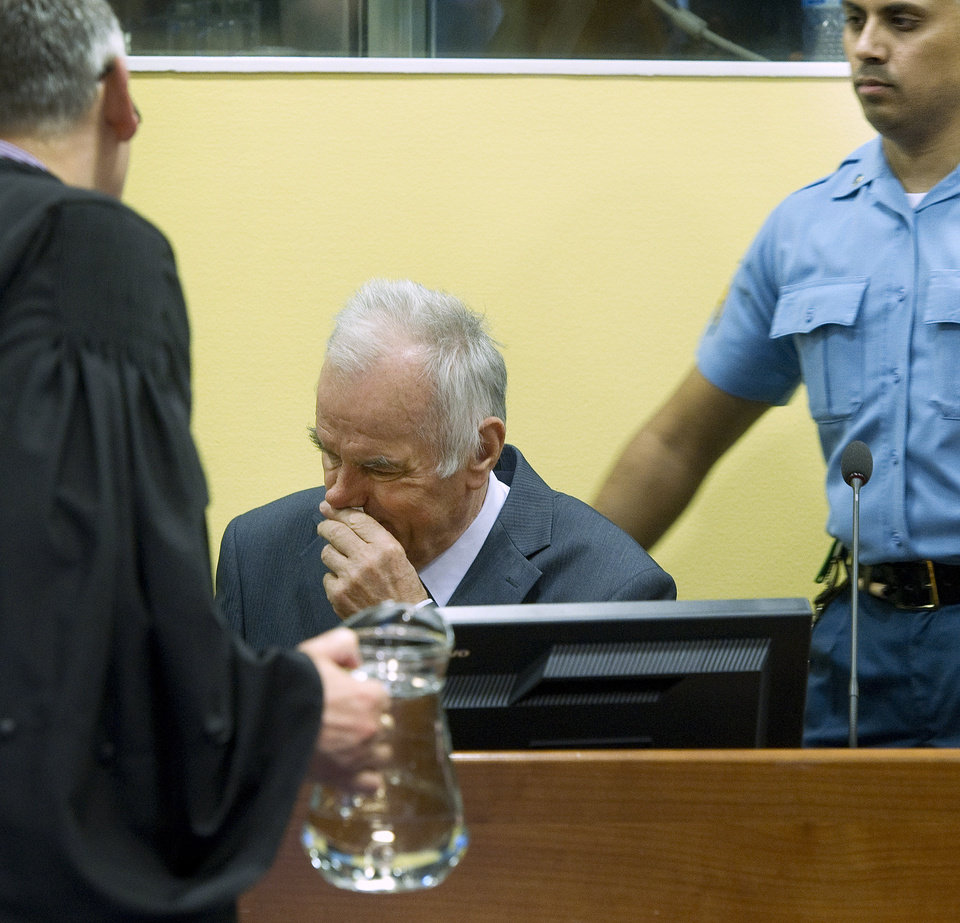 Photo -   Former Bosnian Serb military commander Gen. Ratko Mladic, center, a UN security guard, right, and member of his defense, left, are seen at the start of his trial at the Yugoslav war crimes tribunal in The Hague, Netherlands, Wednesday May 16, 2012. Twenty years after the opening shots of the Bosnian War, Mladic has gone on trial on charges of genocide, crimes against humanity and war crimes, his appearance at the UN tribunal marks the end of a long wait for justice to survivors of the 1992-95 war that left some 100,000 people dead. (AP Photo/Toussaint Kluiters, Pool)