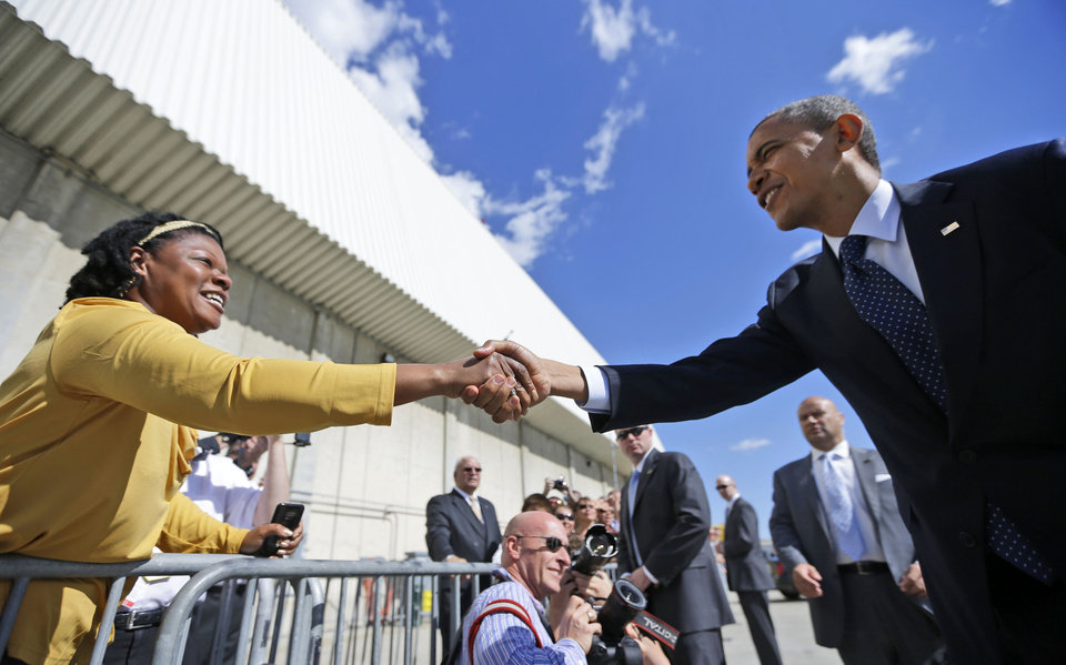 Photo -   President Barack Obama reaches over to greet a supporters on the tarmac upon his arrival on Air Force One, Monday, Sept. 24, 2012, at JFK airport in New York. (AP Photo/Pablo Martinez Monsivais)