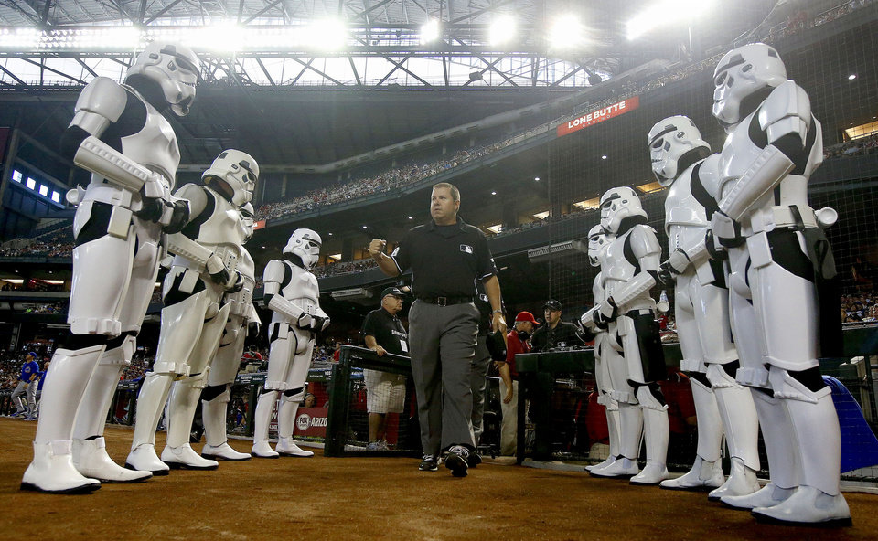 Photo - The umpire crew, lead by Doug Eddings, walks onto the field as they are flanked by people dressed as stormtroopers from the
