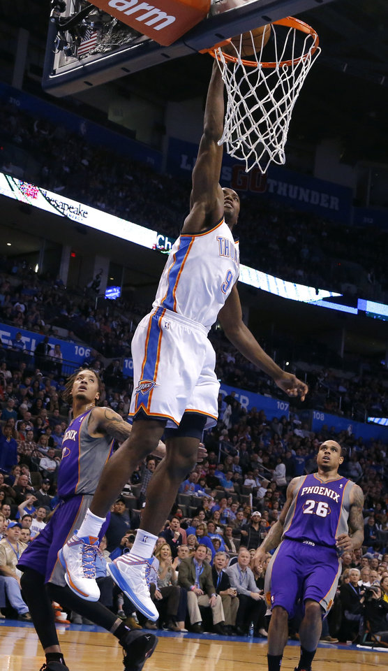 Photo - Oklahoma City's Serge Ibaka (9) dunks in front of Phoenix 's Channing Frye (8) and Phoenix 's Shannon Brown during the NBA game between the Oklahoma City Thunder and the Phoenix Suns at theChesapeake Energy Arena, Friday, Feb. 8, 2013.Photo by Sarah Phipps, The Oklahoman