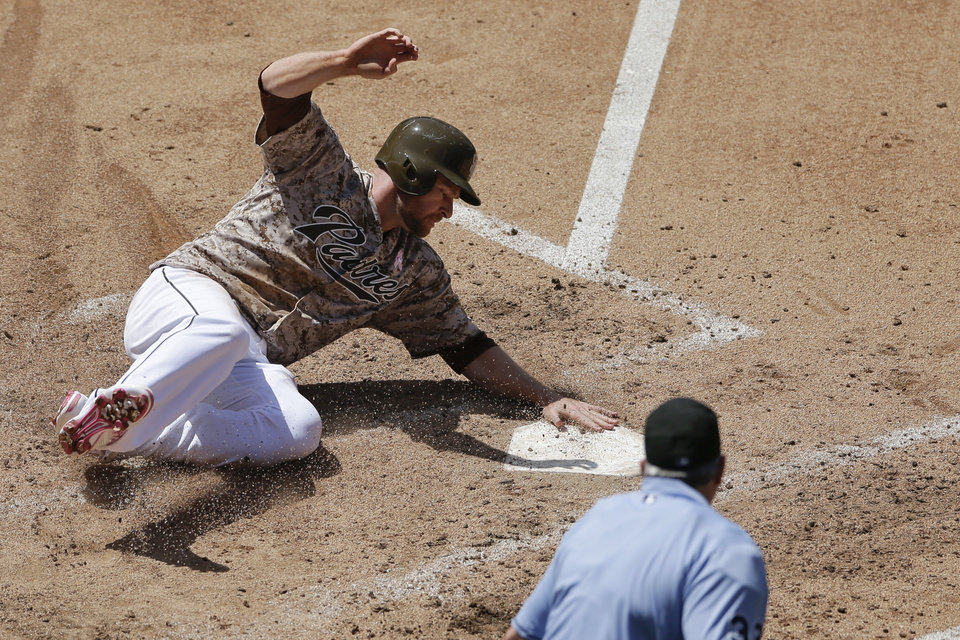 Photo - San Diego Padres' Chase Headley touches home plate as he scores off a hit for a single by teammate Alexi Amarista while playing the Miami Marlins during the fourth inning of a baseball game Sunday, May 11, 2014, in San Diego. (AP Photo/Gregory Bull)