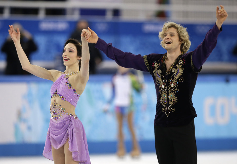 Photo - Meryl Davis and Charlie White of the United States acknowledge the crowd after completing their routine in the ice dance free dance figure skating finals at the Iceberg Skating Palace during the 2014 Winter Olympics, Monday, Feb. 17, 2014, in Sochi, Russia. (AP Photo/Darron Cummings)