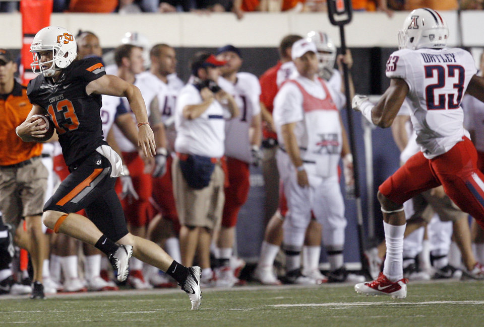 Photo - Oklahoma State's Quinn Sharp runs a fake punt as Arizona's Mark Watley chases him during the third quarter of the Cowboys win Thursday. PHOTO BY SARAH PHIPPS, The Oklahoman