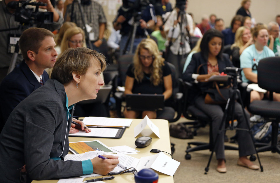 Photo - The Environmental Protection Agency's Jenny Noonan listens to testimony on the first of two days of public hearings held by the EPA on President Barack Obama's plan to cut carbon dioxide emissions by 30 percent by 2030, in Denver, Tuesday, July 29, 2014. In hearings, hundreds of people across the country are telling the EPA its new rules for power-plant pollution either go too far or not far enough. (AP Photo/Brennan Linsley)