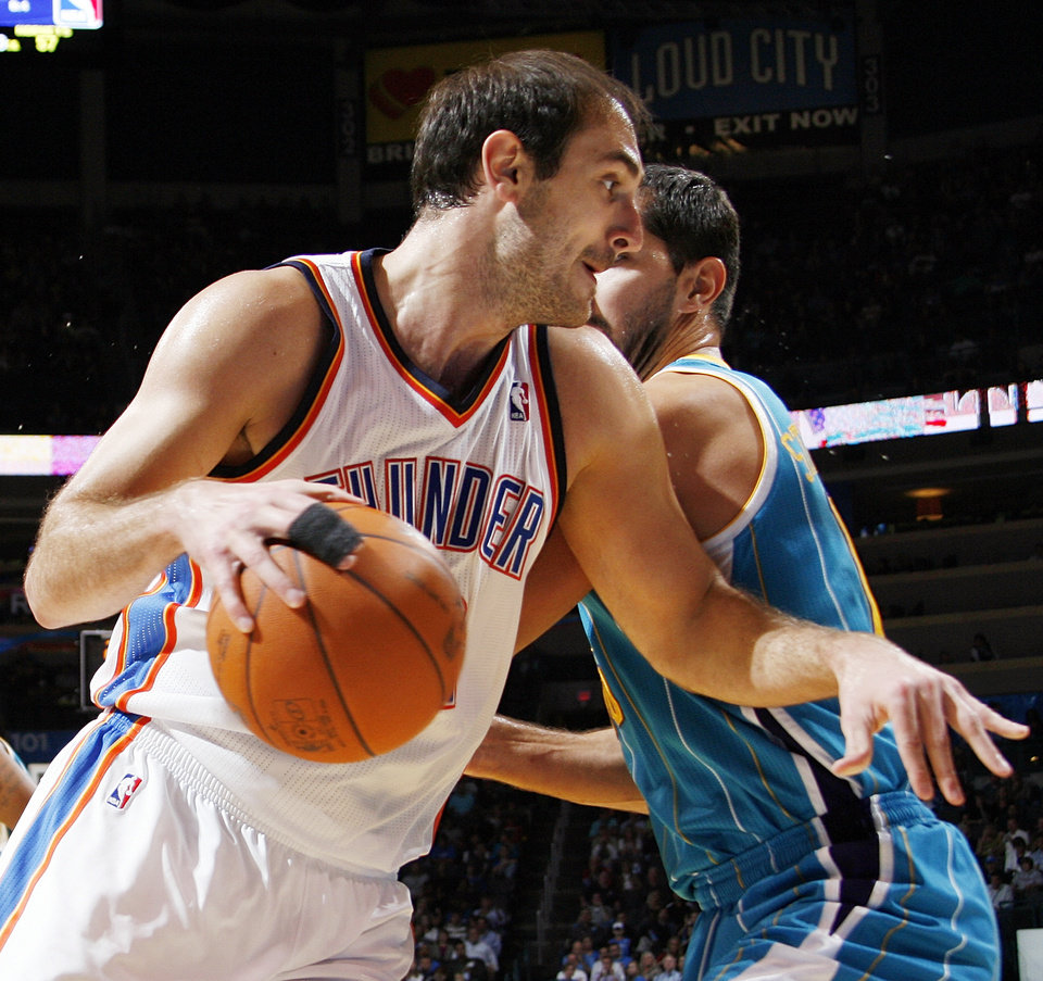 Photo - Oklahoma City's Nenad Krstic (12) tries to get past Peja Stojakovic (16) of New Orleans during the preseason NBA basketball game between the New Orleans Hornets and the Oklahoma City Thunder at the Ford Center in Oklahoma City, Thursday, October 21, 2010. The Thunder won, 101-86. Photo by Nate Billings, The Oklahoman