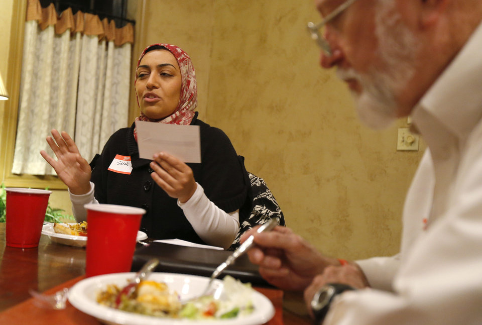 Photo - Sarah Albahadily reads a question during a recent Amazing Faiths  interfaith dinner in the Edmond area. Photo by Bryan Terry, The Oklahoman   BRYAN TERRY - THE OKLAHOMAN