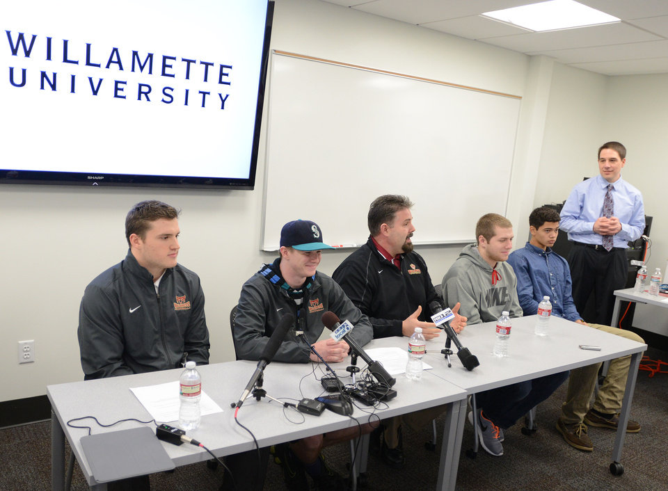 Photo - Conner Mertens, second from left, a redshirt freshman place kicker at Willamette University, attends a news conference at the university in Salem, Ore., on Tuesday, Jan. 28, 2014. Defensive captain Jack Nelson, left, coach Glen Fowles, center, and others joined Mertens. Merters announced that he is bisexual, saying he was tired of pretending he was something he wasn't. (AP Photo/Statesman Journal, Danielle Peterson)
