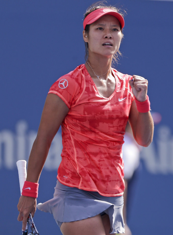 Photo - Li Na, of China, reacts after a point against Ekaterina Makarova, of Russia, during the quarterfinals of the 2013 U.S. Open tennis tournament, Tuesday, Sept. 3, 2013, in New York. (AP Photo/Julio Cortez)