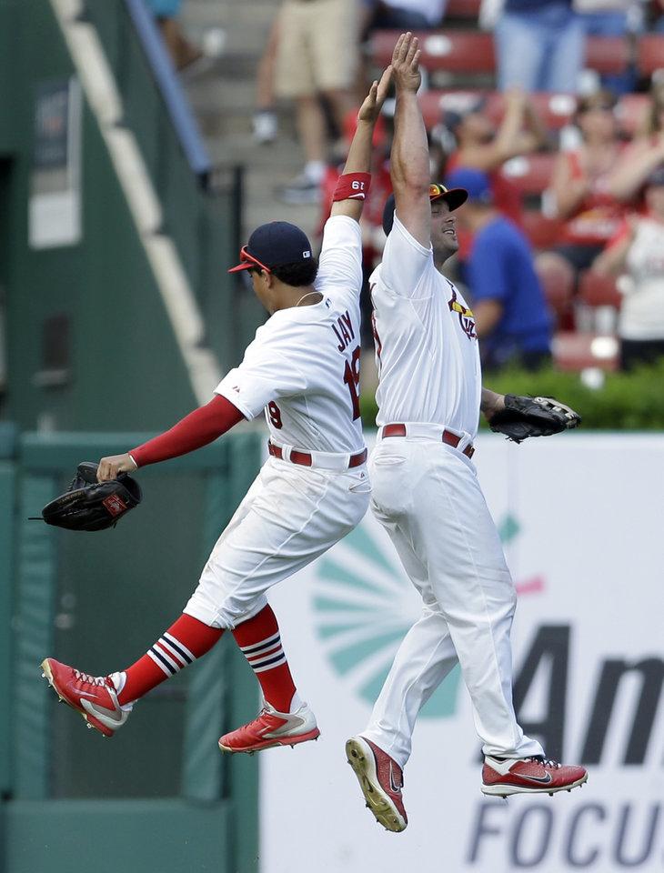 Photo - St. Louis Cardinals' Matt Holliday, right, and teammate Jon Jay celebrate following the Cardinals' 9-6 victory over the Chicago Cubs in a baseball game Sunday, Aug. 31, 2014, in St. Louis. (AP Photo/Jeff Roberson)