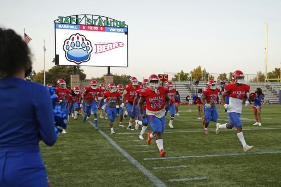 Photo -  The John Marshall team takes the field before a high school football game against Blanchard at Taft Stadium on Thursday. [Bryan Terry/The Oklahoman]