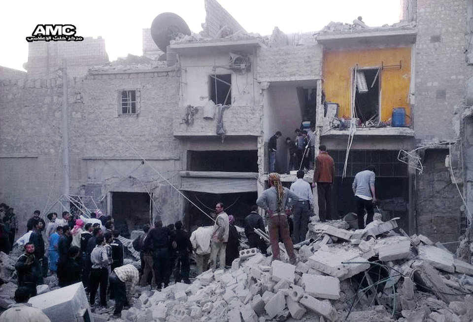 Photo - In this Monday, March 18, 2013, citizen journalism image provided by Aleppo Media Center AMC which has been authenticated based on its contents and other AP reporting, Syrian citizens stand on rubble of houses that were destroyed due to Syrian forces airstrikes, at al-Marjeh neighborhood, in Aleppo, Syria. Syrian information minister says chemical weapon fired is 'first act' by interim government. (AP Photo/Aleppo Media Center, AMC)