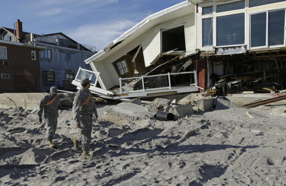 National Guardsmen Specialist Ivan Pimentel, left, and PFC Harry Cadet walk along the beach past a destroyed house during a break in their work in the Rockaways, Thursday, Jan. 10, 2013, in New York.  The guardsmen said they were working with the New York City Office of Emergency Management going door-to-door to determine if residents needed portable heaters or other items to in the wake of Superstorm Sandy. Using portable personal tablets, they said they could provide residents with a heater within 30 minutes. (AP Photo/Kathy Willens)