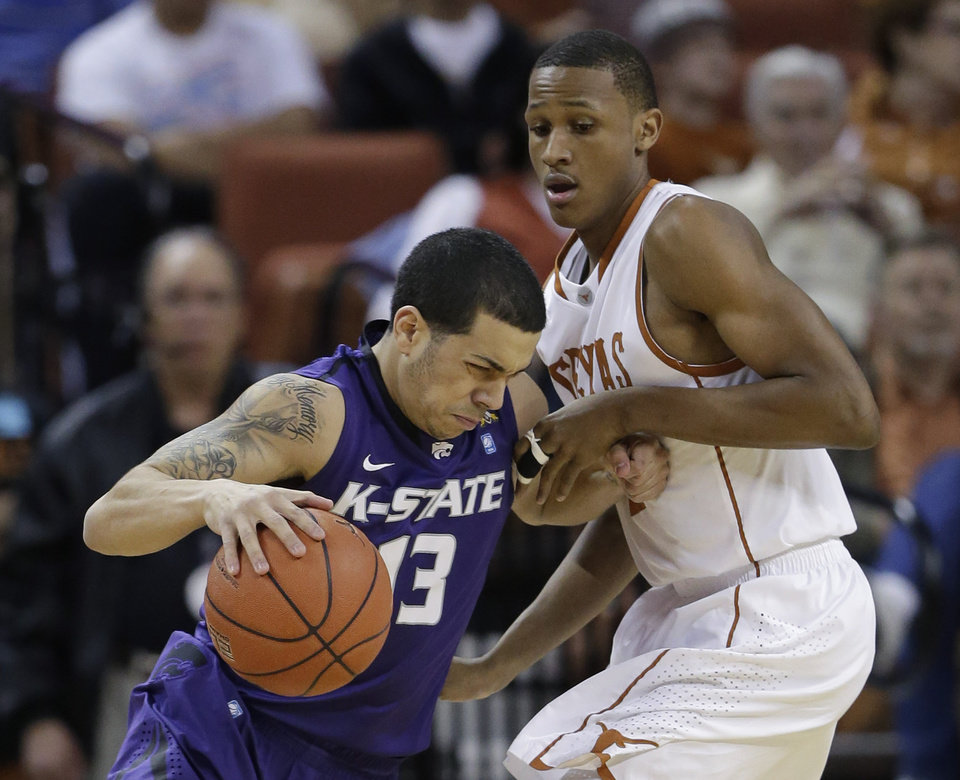 Photo - Kansas State's Angel Rodriguez (13) is pressured by Texas' Demarcus Holland, right, during the first half on an NCAA college basketball game, Saturday, Feb. 23, 2013, in Austin, Texas. (AP Photo/Eric Gay)
