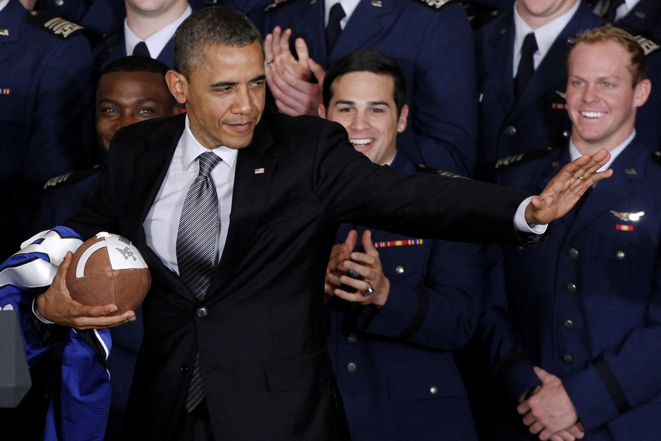 """FILE- In this April 23, 2012 file photo, President Obama strikes the Heisman pose after he awarded the Commander-in-Chief Trophy to the Air Force Academy football team at the White House in Washington. """"I\'m a big football fan, but I have to tell you, if I had a son, I\'d have to think long and hard before I let him play football,"""" President Barack Obama tells The New Republic. In an interview in the magazine's Feb. 11 issue, Obama says he worries more about college players than he does about those in the NFL. (AP Photo/Charles Dharapak, File)"""