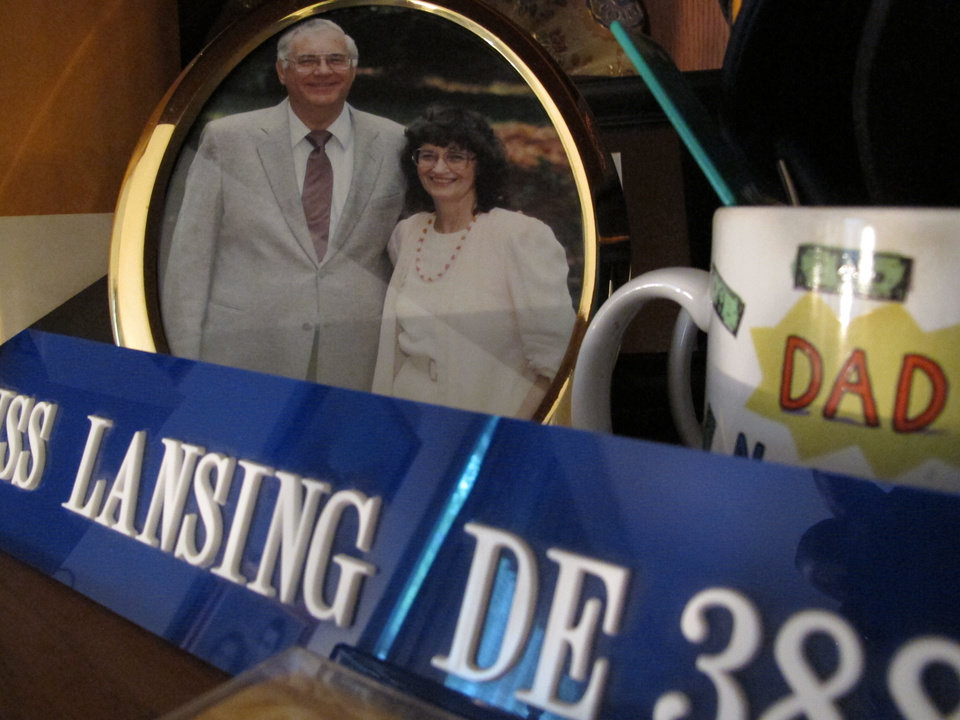 This Thursday, April 19, 2012 photo shows a framed picture and other mementoes of Charles and Miriam Parker in their Raleigh, N.C., home. In the foreground is a plaque bearing the name of the ship he served on during World War II. The couple were ensnared by an international sweepstakes scam that took their family years to unravel. (AP Photo/Allen Breed)