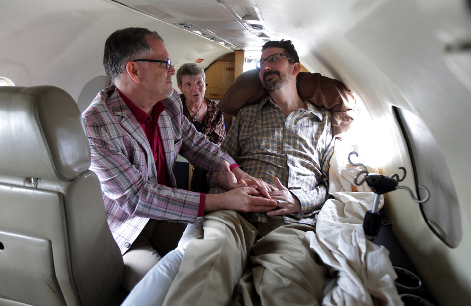 Photo - In this photo made Thursday, July 11, 2013, officiant Paulette Roberts, rear center, marries Jim Obergefell, left and John Arthur, who suffers from MLS, is bedridden and in hospice care, on a plane on the tarmac at Baltimore/Washington International Thurgood Marshall Airport in Glen Burnie, Md. A federal judge has ruled in favor of the two Ohio men who want their out-of-state marriage recognized as John nears death, a case that's seen as encouraging for same-sex marriage supporters in Ohio. (AP Photo/The Cincinnati Enquirer, Glenn Hartong) MANDATORY CREDIT, NO SALES