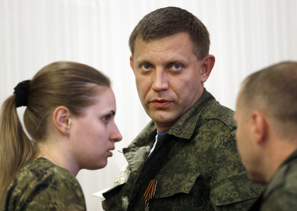 Photo - Prime Minister of the self-proclaimed Donetsk People's Republic Alexander Zakharchenko, center, leaves a news conference in Donetsk, eastern Ukraine, Sunday, Aug. 24, 2014. Ukraine has retaken control of much of its eastern territory bordering Russia in the last few weeks, but fierce fighting for the rebel-held cities of Donetsk and Luhansk persists. (AP Photo/Sergei Grits)