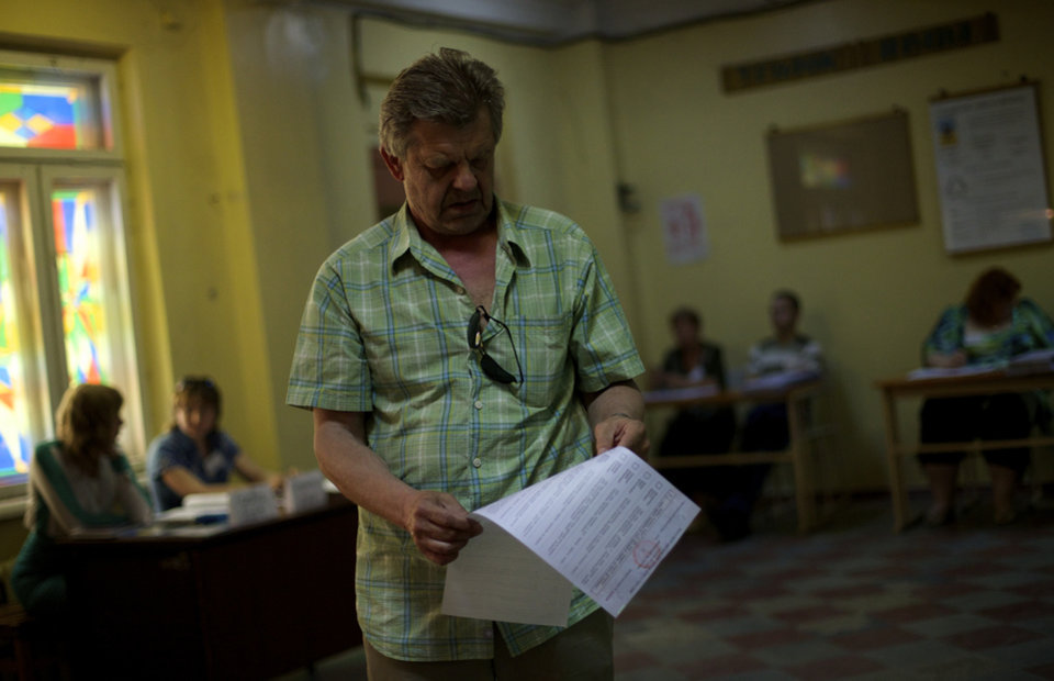 Photo - An Ukrainian man looks at his ballot at a polling station in Mariupol, Ukraine, on Sunday, May 25, 2014. Ukraine's critical presidential election got underway Sunday under the wary scrutiny of a world eager for stability in a country rocked by a deadly uprising in the east. (AP Photo/Ivan Sekretarev)