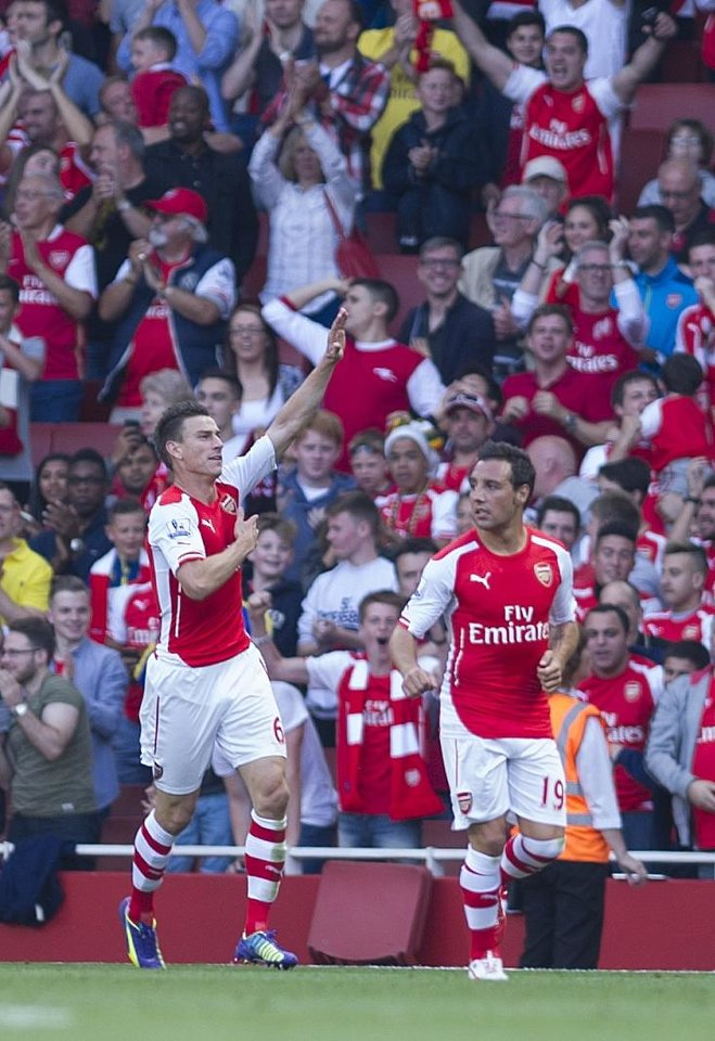 Photo - Arsenal's Laurent Koscielny, left, celebrates with teammate Santi Cazorla after scoring against Crystal Palace, during their English Premier League soccer match, at Emirates Stadium, in London, Saturday, Aug. 16, 2014. (AP Photo/Bogdan Maran)