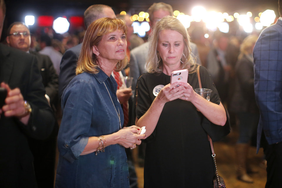 Photo - Abby LaForge, left, and Leann Stanton, both of Chickasha, Okla., watch election results during the Republican election night watch party for the 2018 elections at the Bricktown Events Center in Oklahoma City, Nov. 6, 2018. Photo by Bryan Terry, The Oklahoman
