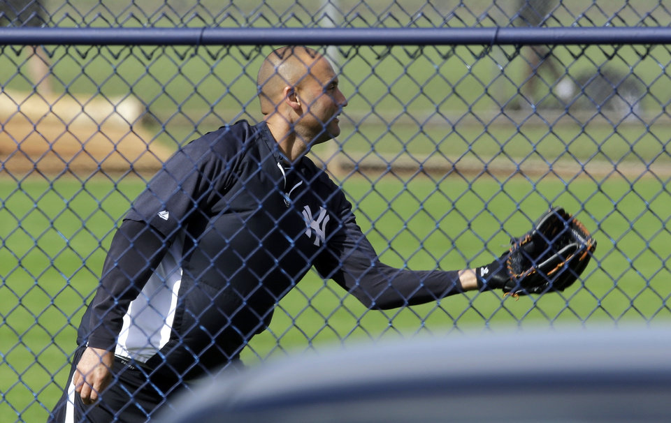 Photo - New York Yankees shortstop Derek Jeter plays catch during a workout at the baseball team's minor league facility  Thursday, Feb. 13, 2014, in Tampa, Fla. Jeter announced he will be retiring at the end of the 2014 season. (AP Photo/Chris O'Meara)