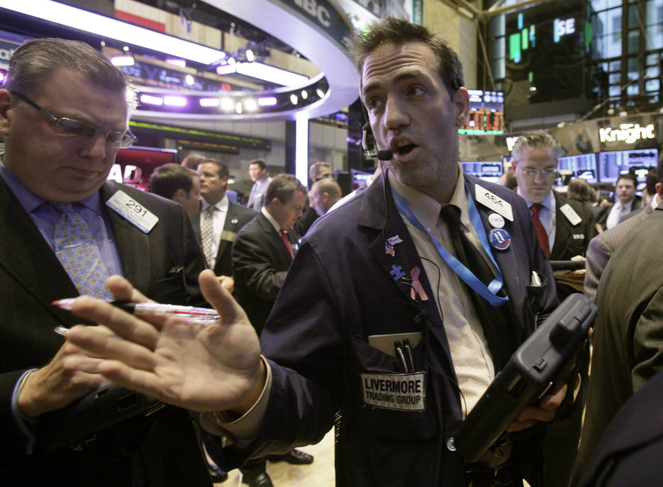 Photo -   Trader Gregory Rowe, center, works on the floor of the New York Stock Exchange Friday, Oct. 5, 2012. Stocks are rising in early trading on Wall Street after the government reported that the U.S. unemployment rate fell below 8 percent for the first time in almost four years. (AP Photo/Richard Drew)