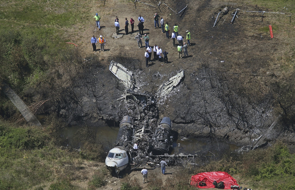 Photo - This aerial photo shows wreckage from where a plane plunged down and erupted in flames during a takeoff attempt at Hanscom Field on Saturday night, Monday, June 2, 2014, in Bedford, Mass. Lewis Katz, co-owner of The Philadelphia Inquirer, and six other people died in the crash. (AP Photo/The Boston Globe, David L. Ryan)  BOSTON HERALD OUT, QUINCY OUT; NO SALES MANDATORY CREDIT.