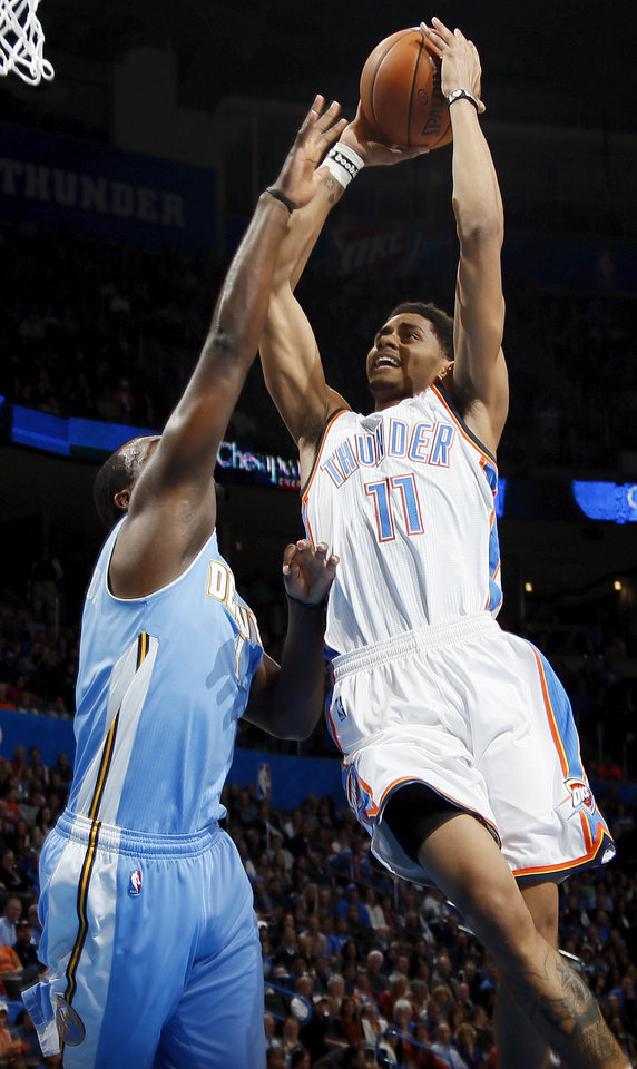 Photo - Oklahoma City's Jeremy Lamb (11) shoots against Denver's Jordan Hamilton (1) during an NBA basketball game between the Oklahoma City Thunder and the Denver Nuggets at Chesapeake Energy Arena in Oklahoma City, Monday, Nov. 18, 2013. Photo by Nate Billings, The Oklahoman