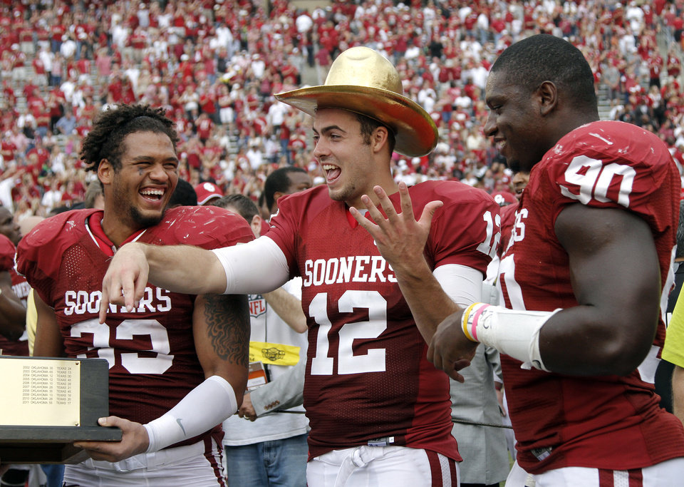 Photo - OU's Landry Jones (12) wears the Golden Hat Trophy with teammates OU's Trey Millard (33) and David King (90) during the Red River Rivalry college football game between the University of Oklahoma (OU) and the University of Texas (UT) at the Cotton Bowl in Dallas, Saturday, Oct. 13, 2012. Photo by Chris Landsberger, The Oklahoman
