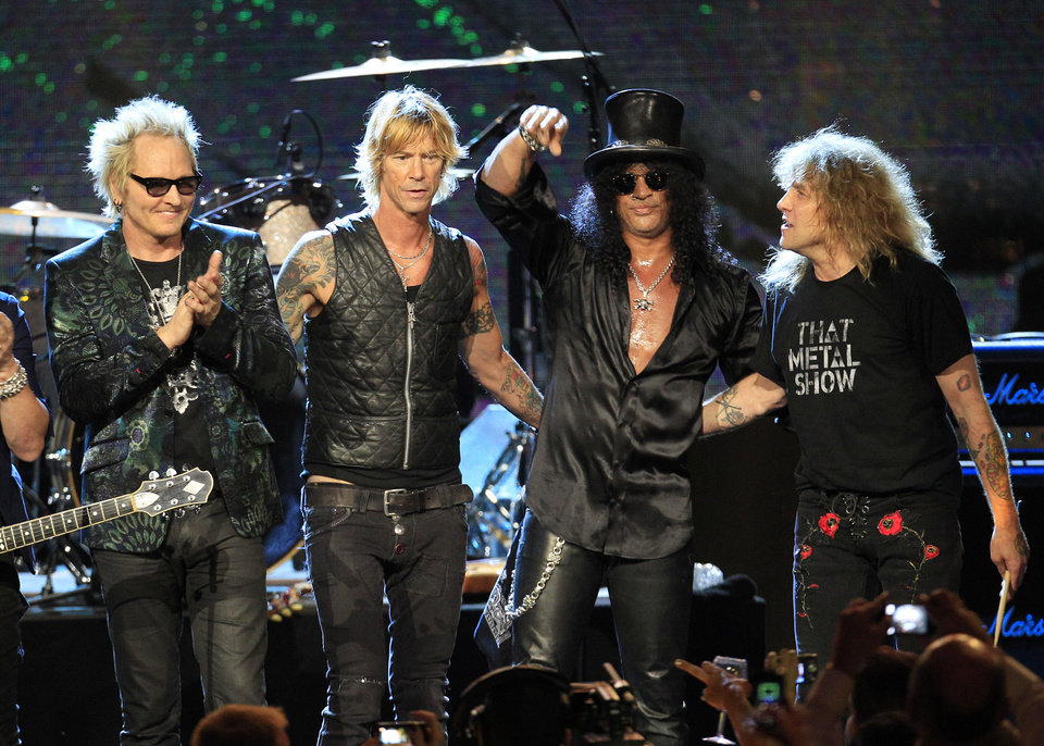 Photo - FILE - This April 15, 2012 file photo shows Guns N' Roses, from left, Matt Sorum, Duff McKagan, Slash and Steven Adler, after their performance following induction into the Rock and Roll Hall of Fame, in Cleveland. Frontman Axl Rose decided to skip the ceremony because it didn't