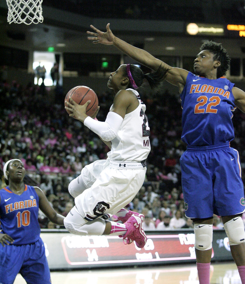 Photo - South Carolina's Tiffany Mitchell, center, drives for the basket as Florida's Kayla Lewis, right, tries to block during the first half of their NCAA women's college basketball game, Sunday, Feb. 23, 2014, in Columbia, S.C. Looking on is Florida's Jaterra Bonds (10). (AP Photo/Mary Ann Chastain)
