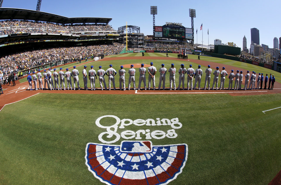 Photo - The Chicago Cubs line up along the first base line during opening day ceremonies before the baseball game between the Pittsburgh Pirates and the Chicago Cubs on Monday, March 31, 2014, in Pittsburgh. (AP Photo/Gene Puskar)