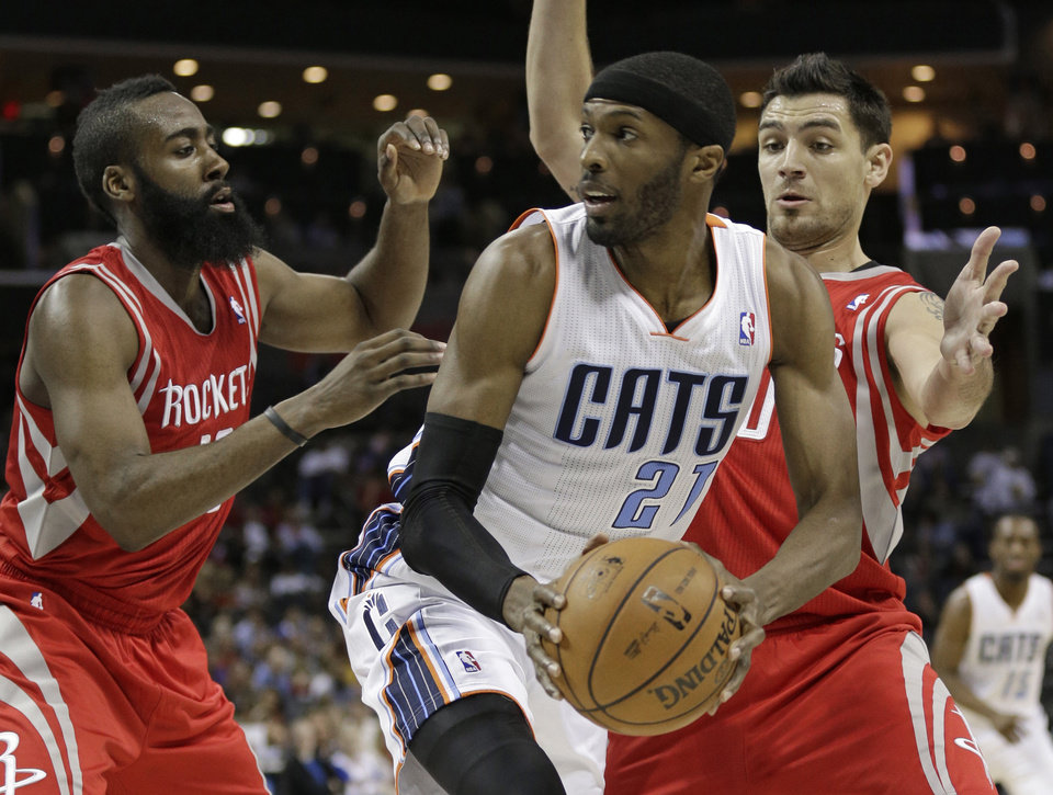 Charlotte Bobcats' Hakim Warrick, center, looks to pass as he is trapped by Houston Rockets' Carlos Delfino, right, and James Harden, left, during the first half of an NBA basketball game in Charlotte, N.C., Monday, Jan. 21, 2013. (AP Photo/Chuck Burton)