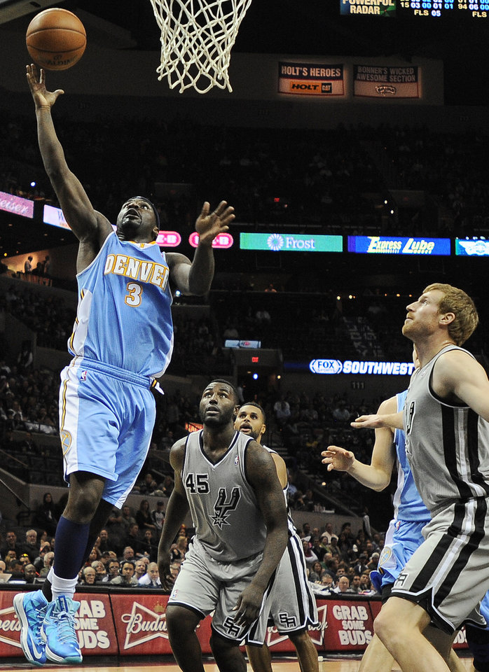 Denver Nuggets' Ty Lawson (3) shoots in front of San Antonio Spurs' DeJuan Blair (45) and Matt Bonner during the second half of an NBA basketball game, Saturday, Nov. 17, 2012, in San Antonio. The Spurs won 126-100. (AP Photo/Darren Abate)