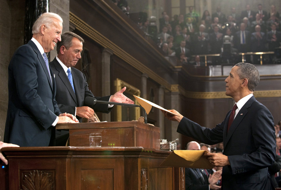 Photo - President Barack Obama hands copies of his speech to House Speaker John Boehner as Vice President Joe Biden watches before Obama delivers his State of the Union address on Capitol Hill in Washington, Tuesday, Jan. 24, 2012. (AP Photo/Saul Loeb, Pool) ORG XMIT: WX166