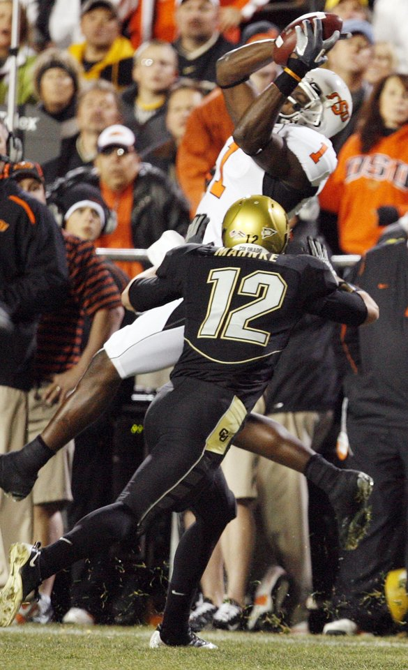 Photo - OSU's Dez Bryant (1) leaps for the ball but cannot hang on as Colorado's Patrick Mahnke (12) defends in the first half during the college football game between Oklahoma State University and University of Colorado at Folsom Field in Boulder, Colo., Saturday, Nov. 15, 2008. BY NATE BILLINGS, THE OKLAHOMAN