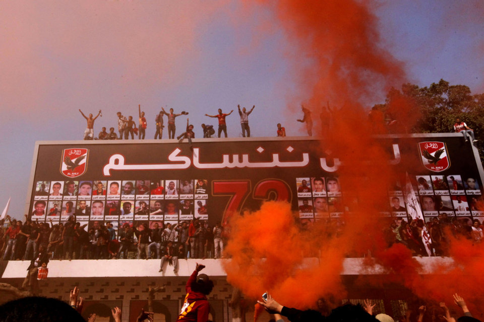 Photo - Egyptian soccer fans of Al-Ahly club celebrate in front of their club in Cairo, Egypt, Saturday, March 9, 2013 after an Egyptian court confirmed death sentences against 21 people for their role in a deadly 2012 soccer riot that killed more than 70 people in the city of Port Said. Banner at background shows pictures of the victims with Arabic reading,