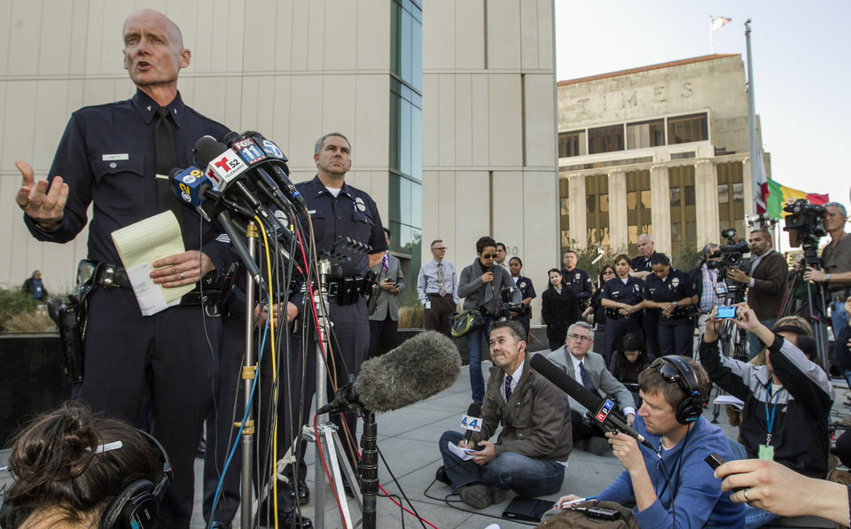 Photo - Los Angeles Police Commander Andrew Smith, left, briefs the media about the shootout scene in Big Bear that allegedly involves triple-murder suspect Christopher Jordan Dorner, during a news conference in front of the Police Administration Building in Los Angeles Tuesday, Feb. 12, 2013. (AP Photo/Damian Dovarganes)