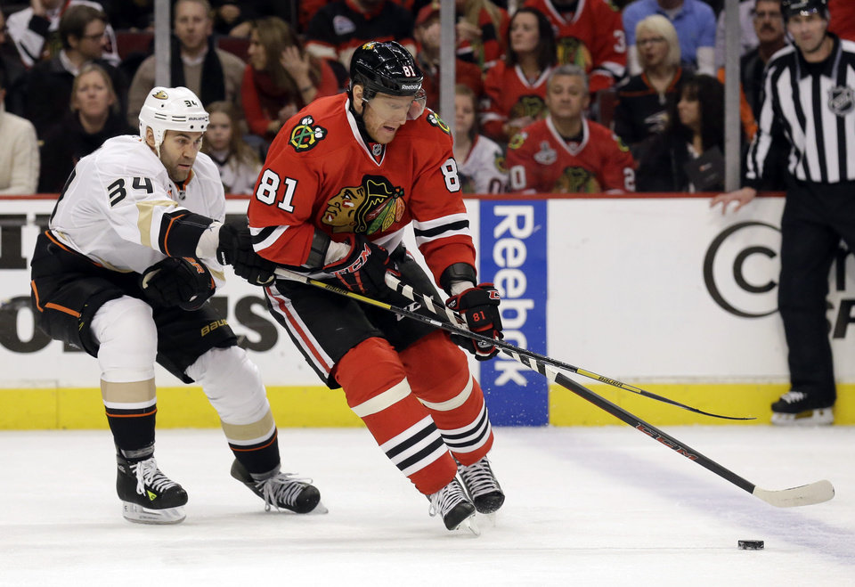 Photo - Chicago Blackhawks' Marian Hossa, right, controls the puck against Anaheim Ducks' Daniel Winnik during the second period of an NHL hockey game in Chicago, Friday, Jan. 17, 2014. (AP Photo/Nam Y. Huh)