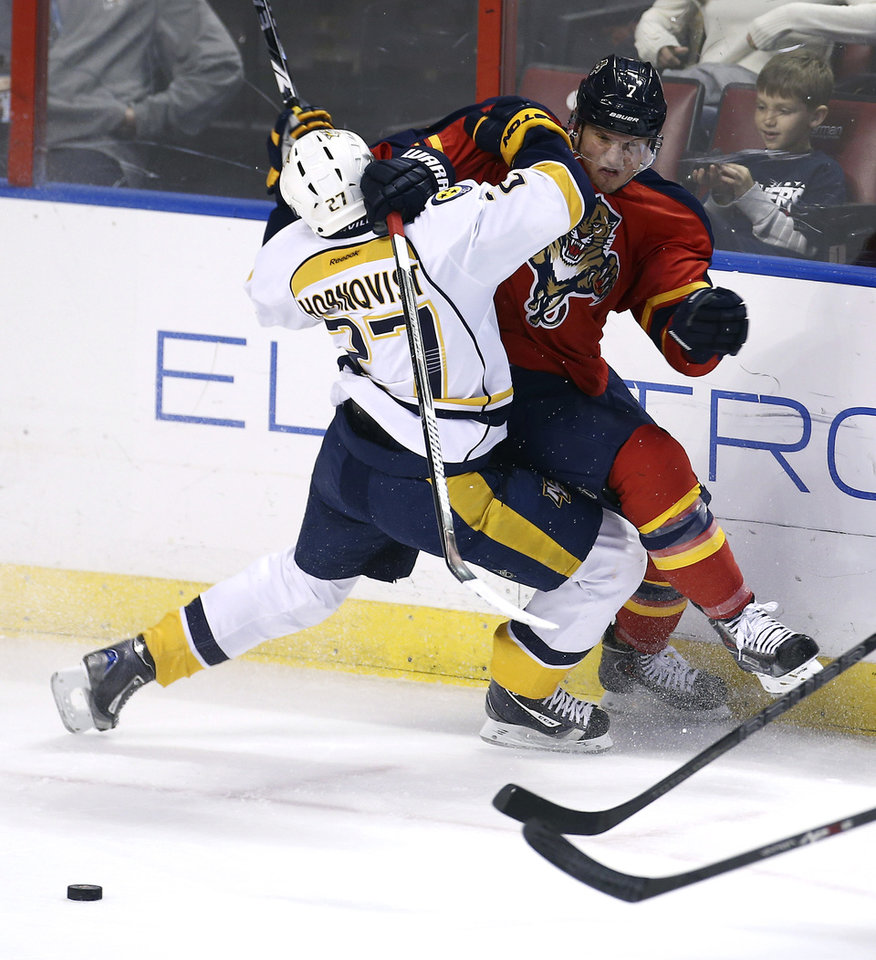 Photo - Nashville Predators' Patric Hornqvist (27) and Florida Panthers' Dmitry Kulikov (7) battle for the puck during the second period of a NHL hockey game in Sunrise, Fla., Saturday, Jan. 4, 2014. (AP Photo/J Pat Carter)