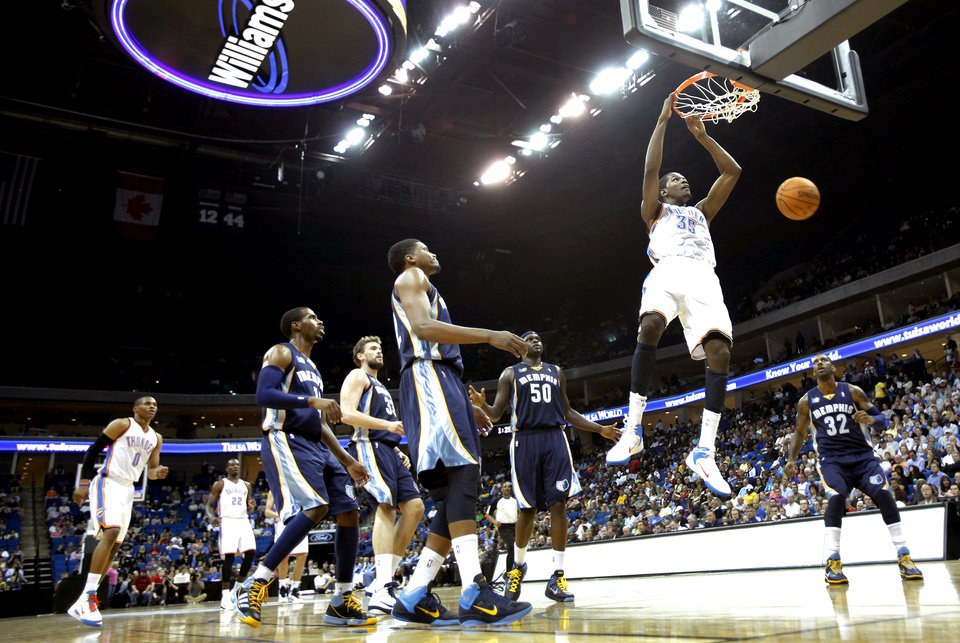 Photo - Oklahoma City's Kevin Durant (35) dunks the ball against Memphis during the first half of the preseason NBA basketball game between the Oklahoma City Thunder and the Memphis Grizzlies on Tuesday, Oct. 12, 2010, in Tulsa, Okla.  Photo by Chris Landsberger, The Oklahoman