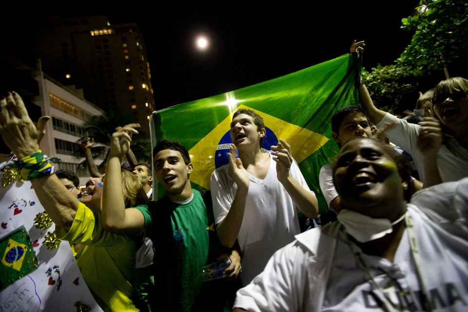 Photo - People shout slogans during an anti-government protest at Ipanema beach in Rio de Janeiro, Brazil, Friday, June 21, 2013. The country's president, who is a former leftist guerrilla, has done little more than show brief support for the protesters since the demonstrations began a week ago. That's brought criticism that she has allowed the situation to spiral out of control. Rousseff was to meet Friday, with bishops from the Catholic Church about the possible impact of the protests on a papal visit that is still scheduled next month. (AP Photo/Silvia Izquierdo)
