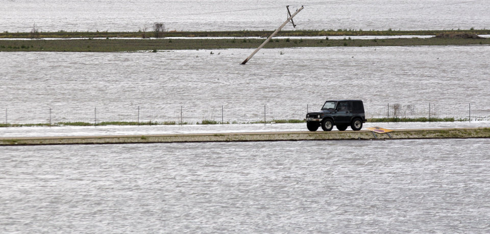 Photo - A car drives down a road between flooded fields on Wednesday, April 27, 2011, in West Memphis, Ark. Strong storms hit the South Wednesday for the second straight day. (AP Photo/Mark Humphrey)