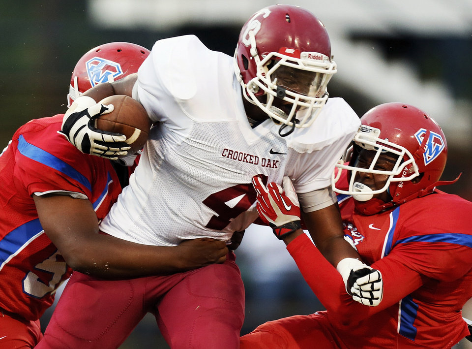 Crooked Oak's Shauntrel Skanes (4) is brought down after a carry by John Marshall's Juan Hill (53), left, and Joseph Shells (10) during a high school football game between John Marshall and Crooked Oak at Star Spencer's Carl Twidwell Stadium, 3001 NE Spencer Rd., in Spencer, Okla., Thursday, Sept. 19, 2013. Photo by Nate Billings, The Oklahoman