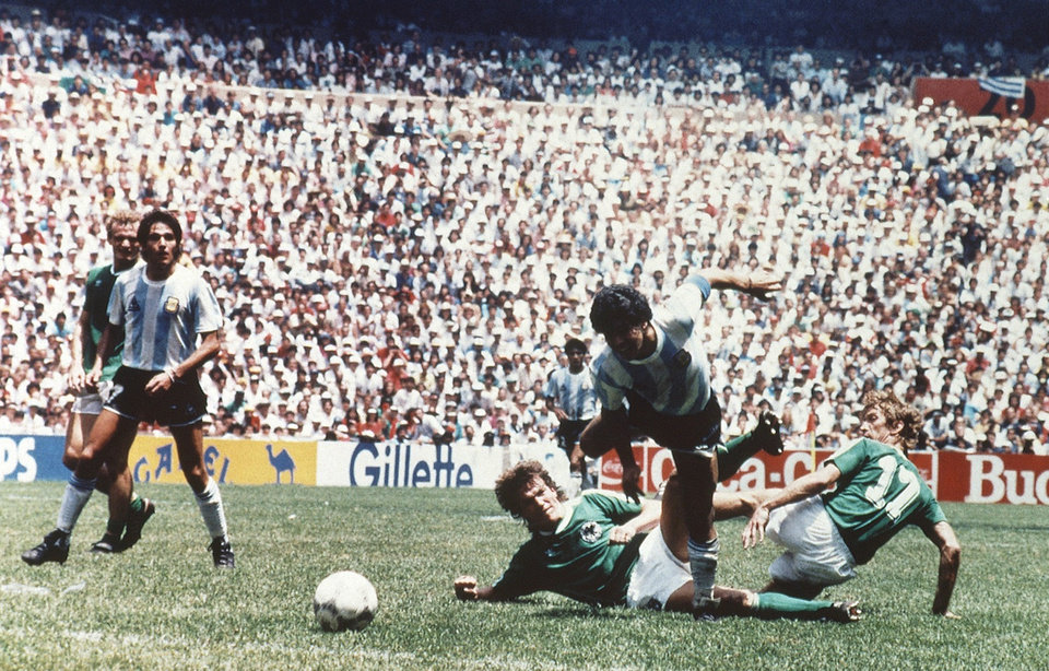 Photo - FILE - The June 29, 1986 file photo shows Argentina's Diego Maradona dribbling past West German players during the World Cup Soccer Final match between Argentina and West Germany at Azteca Stadium in Mexico City, Mexico. On Sunday, July 13, 2014, Germany and Argentina will face each other again in the final of the 2014 soccer World Cup. (AP Photo/file)