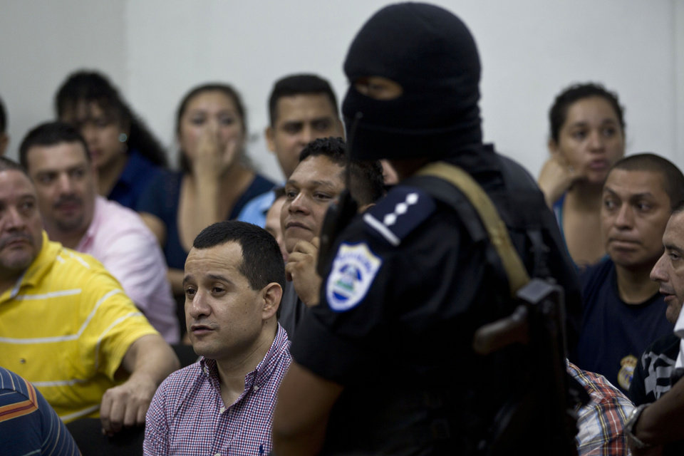 A masked police officer stands guard as Henry Farinas sits with accused during the reading of their sentences on charges of money laundering in Managua, Nicaragua, Friday, Oct. 12, 2012. A Nicaraguan judge handed down a 30-year sentence for money-laundering to Farinas who was allegedly targeted when gunmen killed Argentine folk singer Facundo Cabral. Prosecutors say a trafficking gang believed Farinas had betrayed it and tried to kill him as he accompanied Cabral in a vehicle after a July 2011 concert in Guatemala that Farinas organized. (AP Photo/Esteban Felix)