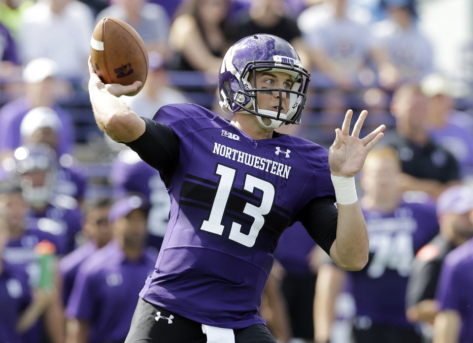 Photo - Northwestern quarterback Trevor Siemian (13) looks to a pass during the first half of an NCAA college football game against California in Evanston, Ill., Saturday, Aug. 30, 2014. (AP Photo/Nam Y. Huh)
