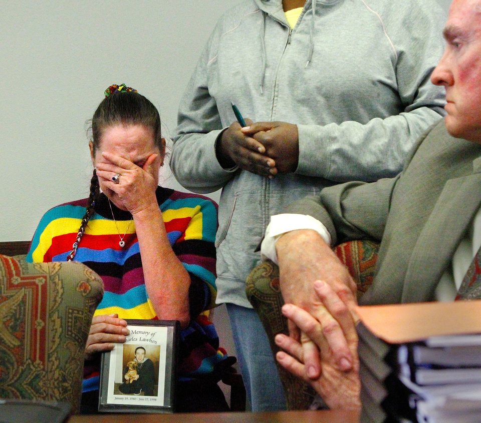 "Dana Lawhon of Oklahoma City covers her face, composing herself after becoming emotional after addressing DHS commissioners and lawmakers  during a public remarks portion of Tuesday's hearing. She asked several times, ""Why is my son in this box?"" as she lifted the small box (shown here on her lap) containing the ashes of her son, Charles Lawhon, who committed suicide in June of 1998.   At right is Brad Yarbrough, who was named the chairman of the DHS Commission today.   Reps. Richard Morrissette and  Rep. Rep. Mike Sanders led a public hearing at the state Capitol Tuesday, Oct. 25, 2011, looking into complaints and allegations of misconduct and lack of professional services against the Department of Human Services.    Photo by Jim Beckel, The Oklahoman"