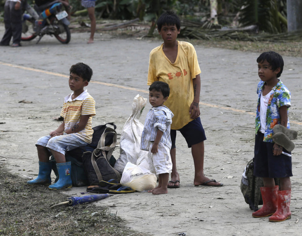 Children wait for a ride to spend the night at an evacuation center a day after Typhoon Bopha swept through the area, in the village of Andap, New Bataan township, Compostela Valley in southern Philippines Wednesday, Dec. 5, 2012. Typhoon Bopha, one of the strongest typhoons to hit the Philippines this year, barreled across the country's south on Tuesday, killing scores of people while triggering landslides, flooding and cutting off power in two entire provinces. (AP Photo/Bullit Marquez)
