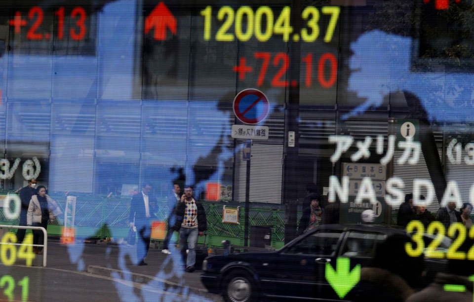 Photo - Passersby are reflected on an electronic board showing Japan's Nikkei 225 index, top, that gained 72.10 points to reach 12,004.37 outside a securities company in Tokyo Thursday, March 7, 2013. Japan's Nikkei 225 index topped 12,000 for the first time in more than four years, but stock markets elsewhere in Asia flagged following Wall Street's eye-popping performance this week. (AP Photo/Shuji Kajiyama)
